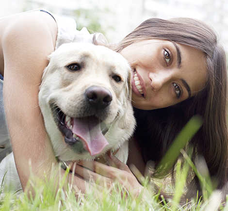 woman smiling with dog in grass