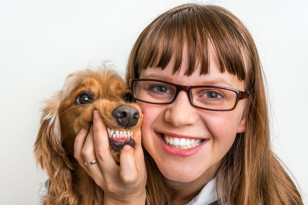 woman with dog and holding open mouth for teeth